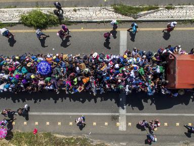 Pemandangan udara saat rombongan imigran Honduras tujuan Amerika Serikat menaiki truk di pinggiran Tapachula, Chiapas, Meksiko, 22 Oktober 2018. Imigran tetap menuju AS meski Presiden Donald Trump sudah merilis pernyataan keras. (PEDRO PARDO/AFP)