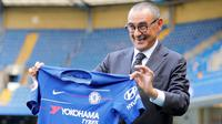 Pelatih baru Chelsea, Maurizio Sarri berpose dengan jersey tim usai konferensi pers di Stamford Bridge di London (18/7). Maurizio Sarri menggantikan pelatih sebelumnya Antonio Conte. (AFP Photo/Tolga Akmen)