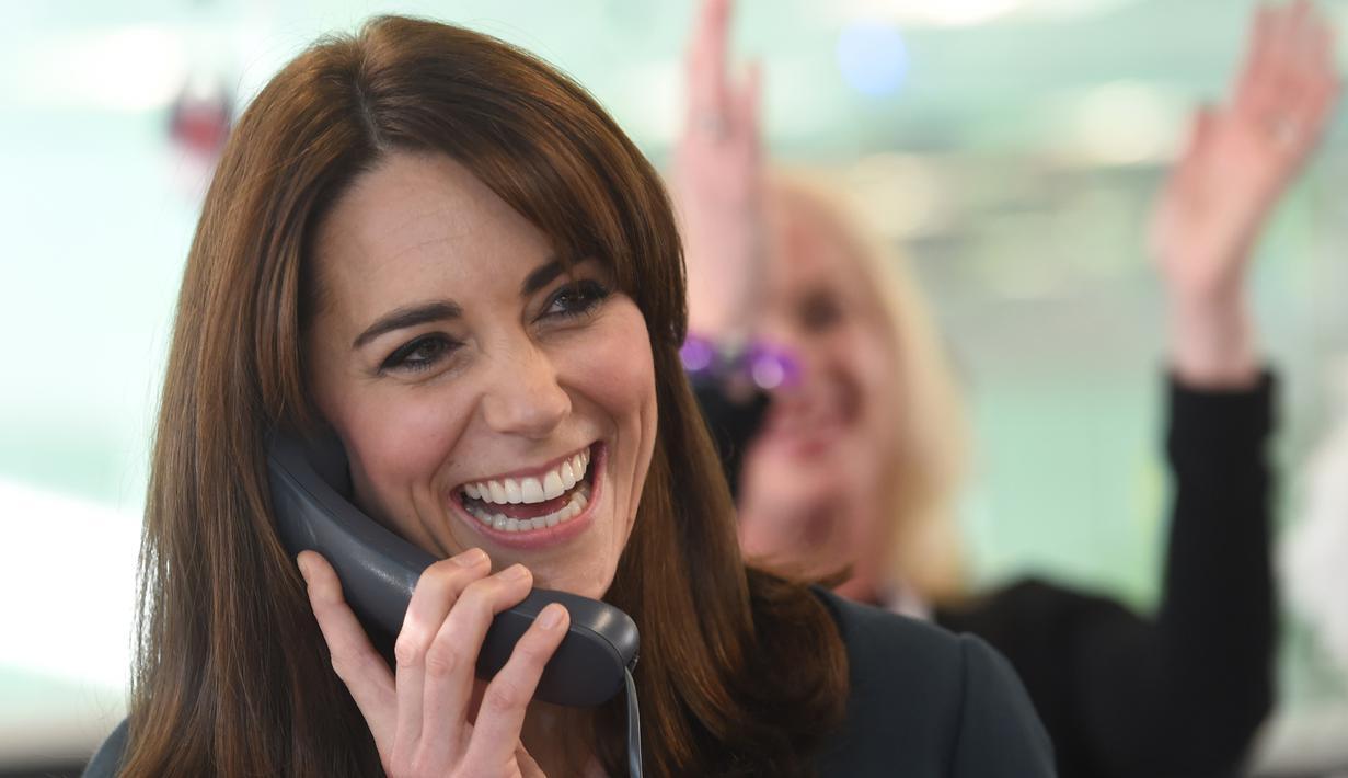 Duchess of Cambridge, Kate Middleton tertawa sambil menggenggam gagang telepon saat menjadi broker dalam acara amal tahunan ICAP di London, Inggris, Rabu (9/12/2015). (AFP PHOTO/POOL/JEREMY Selwyn)