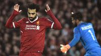 Gelandang Liverpool, Mohamed Salah berselebrasi setelah mencetak gol ke gawang AS Roma pada laga leg pertama semifinal Liga Champions 2017-2018 di Anfield, Selasa (24/4). Liverpool mengalahkan AS Roma di kandang sendiri 5-2. (Filippo MONTEFORTE/AFP)