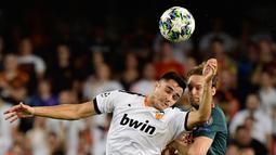 Penyerang Valencia, Maxi Gomez berebut bola dengan bek Ajax Amsterdam, Daley Blind pada lanjutan pertandingan grup H Liga Champions di stadion Mestalla, Spanyol (2/10/2019). Ajax menang telak 3-0 atas Valencia. (AFP Photo/Javier Soriano)