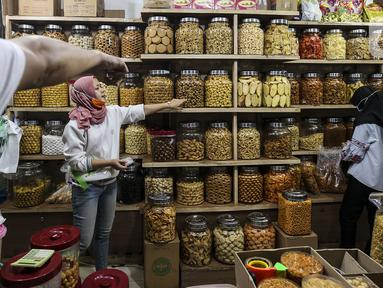 Pedagang kue kering melayani pembeli di Pasar Mayestik, Jakarta, Senin (3/5/2021). Omzet penjualan kue kering menjelang Lebaran tahun ini mengalami peningkatan hingga 70 persen dari tahun sebelumnya yang mengalami penurunan hingga 70 persen. (Liputan6.com/Johan Tallo)