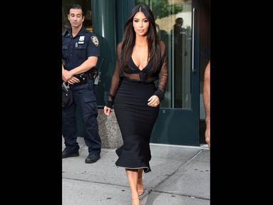 Seorang petugas tak melepaskan pandangannya saat melihat Kim Kardashian melangkah keluar dari apartemennya di New York City, Minggu (10/8/14). (Dailymail)