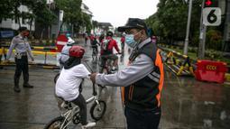 Petugas Dishub mengatur pesepeda saat uji coba penerapan zona rendah emisi di Kota Tua, Jakarta, Minggu (20/12/2020). Selama penerapan zona rendah emisi, kawasan Kota Tua hanya bisa dilalui pejalan kaki, pesepeda, angkutan umum, dan kendaraan khusus yang lulus uji emisi. (Liputan6.com/Faizal Fanani)