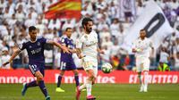 Gelandang Real Madrid, Isco, berusaha melewati bek Valladolid, Javi Moyano, pada laga La Liga di Stadion Santiago Bernabeu, Madrid, Sabtu (24/8). Kedua klub bermain imbang 1-1. (AFP/Gabriel Bouys)