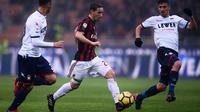 Gelandang AC Milan, Lucas Biglia berusaha membawa bola dari kawalan dua pemain Crotone saat bertanding pada lanjutan Liga Serie A Italia di San Siro, Milan (6/1). Milan menang tipis 1-0 atas Crotone. (AFP Photo/Marco Bertorello)