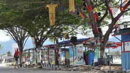 Seorang pria membawa kursi melewati pohon yang berhias barang-barang untuk memperingati gempa dan tsunami Palu, Rabu (3/4). Kondisi Palu mulai membaik setelah bencana gempa dan tsunami melanda melanda enam bulan lalu. (OLAGONDRONK/AFP)