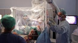 Gambar yang dirilis 19 Februari, musisi Dagmar Turner bermain biola saat berlangsungnya operasi pengangkatan tumor otak di King's College Hospital, London. Tim dokter berhasil mengangkat lebih dari 90 persen tumor dari perempuan 53 itu, termasuk yang paling agresif. (KING'S COLLEGE HOSPITAL/AFP)