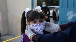Seorang guru menyesuaikan posisi masker seorang pelajar di sekolah pada hari pertama tahun ajaran baru di kamp pengungsi Al-Amari di Kota Ramallah, Tepi Barat (6/9/2020). Pelajar Palestina memulai tahun ajaran baru setelah belajar di rumah selama enam bulan akibat Covid-19. (Xinhua/Nidal Eshtayeh)