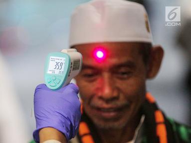 Petugas Kesehatan Karantina Bandara (KKB) memeriksa suhu badan penumpang yang baru mendarat di Terminal 3 Bandara Soekarno Hatta, Tangerang, Banten, Rabu (15/5/2019). Pemeriksaan acak dilakukan untuk mewaspadai adanya penumpang yang terjangkit cacar monyet atau monkeypox. (Liputan6.com/FaizalFanani)