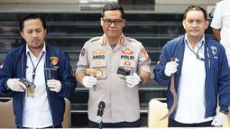 Kabid Humas Polda Metro Jaya Kombes Pol Argo Yuwono (tengah) menunjukkan barang bukti kasus pencurian dengan pemberatan dalam rilis di Polda Metro Jaya, Jakarta, Selasa (23/7/2019). Polisi meringkus empat tersangka pada dua kasus berbeda. (Liputan6.com/Immanuel Antonius)
