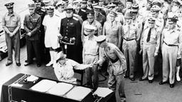 Jenderal AS Douglas MacArthur menyerahkan pena kepada Letnan Inggris Jenderal Arthur E. Percival usai menandatangani surat-surat penyerahan Jepang di atas kapal perang USS Missouri, Teluk Tokyo, 2 September 1945. Penandatanganan ini menandai berakhirnya Perang Dunia II. (Pool Photo via AP, File)