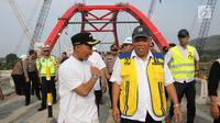 Menteri PUPR Basuki Hadimuljono (kanan) mendengarkan Bupati Batang Wihaji berbicara usai uji coba Jembatan Kali Kuto di Batang, Jateng, Rabu (13/6). Hadi mengatakan Jembatan Kali Kuto akan dioperasikan selama 24 jam. (Liputan6.com/Arya Manggala)
