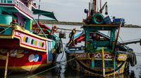 Dua nelayan membawa hasil tangkapannya dari perahu saat tiba di sebuah tempat pelelangan ikan di Brondong, Lamongan, Jawa Timur, Senin (13/3). (AFP Photo/Juni Kriswanto)