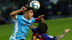 Striker Barcelona, Lionel Messi, duel udara dengan pemain Leganes, Unai Bustinza, pada laga La Liga di Stadion Camp Nou, Selasa (16/6/2020). Barcelona menang 2-0 atas Leganes. (AP Photo/Joan Montfort)