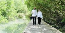 Jokowi dan Iriana tampak romantis berjalan di jembatan yang membelah mangrove di Taman Hutan Raya Ngurah Rai, Bali. Keduanya kompak mengenakan kemeja putih dipadukan celana hitam. Instagram @jokowi.