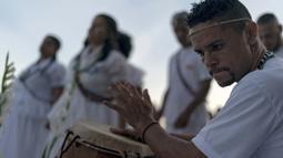 Seorang pria memainkan gendang saat memberi penghormatan kepada Yemenja sang Dewi Laut, ketika menyambut tahun baru di Pantai Copacabana di Rio de Janeiro (29/12/2019). Pengikut Yemanja melakukan ritual tersebut agar mendapat berkat di tahun yang akan datang. (AFP/Mauro Pimentel)