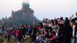 Wisatawan lokal dan asing mengunjungi kuil tua Myanmar sesaat sebelum matahari terbit di Bagan, distrik Nyaung U, Myanmar tengah (16/12). Banyak wisatawan menggunakan balon udara untuk menikmati pemandangan langit Bagan. (AP Photo/Aung Shine Oo)