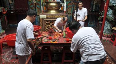 Umat Tionghoa mencuci dan membersihkan sejumlah alat pusaka seperti Pedang dan Golok saat prosesi pensucian tandu (kio) yang digunakan  mengusung arca suci saat perayaan cap go meh, di Vihara Bodhi Dharma, Jakarta, (20/2). (Liputan6.com/Johan Tallo)