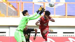 Pemain PSM Makassar, Yakob Sayuri (kanan) berduel udara dengan kiper Barito Putera, Muhammad Riyandi dalam laga pekan ke-5 BRI Liga 1 2021/2022 di Stadion Wibawa Mukti, Cikarang, Senin (27/9/2021). PSM kalah 0-2. (Bola.com/Ikhwan Yanuar)