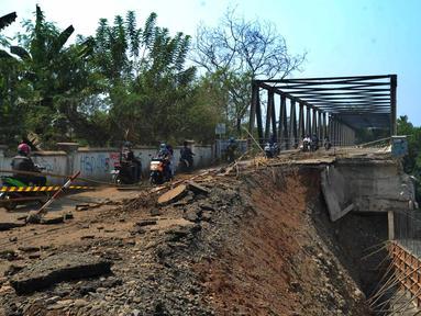 Pengendara roda dua melintasi jalan longsornya tepian jembatan Cipamingkis Cibarusah, Kab Bekasi, Jawa Barat (15/7). Sudah lebih empat bulan jembatan tersebut tertutup bagi kendaraan roda empat. (Merdeka.com/Arie Basuki)