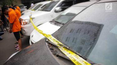 Petugas memasang garis polisi pada puluhan barang bukti mobil yang berhasil disita saat gelar kasus di Polda Metro Jaya, Rabu (18/9/2019). Subdit 6 Ditreskrimum PMJ mengungkap kejahatan penggelapan mobil dengan barang bukti 28 kendaraan roda empat dan sejumlah tersangka. (Liputan6.com/Faizal Fanani)