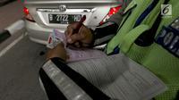 Polisi memberikan surat tilang kepada pengemudi mobil berpelat nomor genap di Jalan S Parman, Jakarta, Rabu (1/8). Polisi hari ini mulai memberlakukan sanksi tilang kepada pelanggar aturan di kawasan perluasan ganjil genap (Liputan6.com/Johan Tallo)