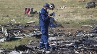 Seorang petugas melakukan penyelidikan di lokasi jatuhnya pesawat Malaysia Airlines MH17 di Desa Hrabove, daerah Donetsk, Ukraina timur. (VOA Indonesia)