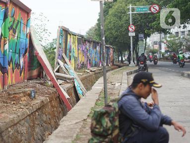 Seorang pria duduk di dekat tembok Jalan Juanda yang ambruk di kawasan Depok, Jawa Barat, Senin (2/12/2019). Kondisi tembok yang dipenuhi mural tersebut mulai rapuh dan sebagian sisinya telah ambruk serta miring sehingga membahayakan pejalan kaki. (Liputan6.com/Immanuel Antonius)