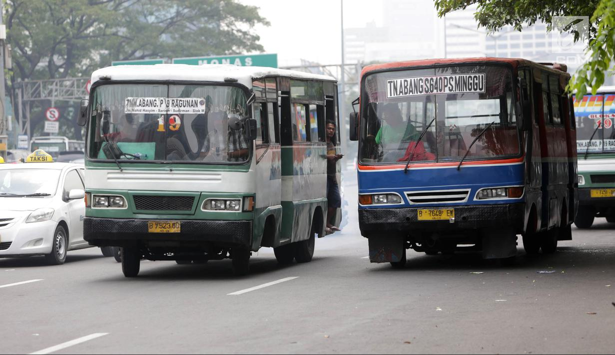Bus Kopaja dan Metromini melintas di Jalan Jenderal Sudirman, Jakarta, Rabu (4/7). Wagub DKI Jakarta Sandiaga Uno melarang angkutan umum seperti Kopaja dan Metromini melintasi jalan protokol selama Asian Games 2018. (Liputan6.com/Arya Manggala)