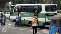 Sejumlah penumpang turun di depan terminal Blok M Jakarta, Kamis (31/3/2016). Pemerintah berencana menurunkan tarif angkutan umum pasca penurunan harga BBM, 1 April mendatang. (Liputan6.com/Helmi Fithriansyah)