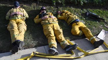 Petugas pemadam kebakaran (damkar) beristirahat setelah kelelahan mengatasi kebakaran yang disebut Lilac Fire di Bonsall, California, Jumat (8/12). Lilac Fire telah menyebar dari 10 hektar menjadi 4.100 hektar hanya dalam beberapa jam. (Robyn Beck/AFP)