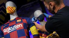 Penjaga toko memasang masker berlogo Barcelona ke Manekin di Toko Asesoris Barcelona, Senin (25/5/2020). Di tengah pandemi virus Corona, Barcelona menjual masker dengan harga 18 euro atau sekitar Rp 291 ribu. (AFP/Lluis Gene)