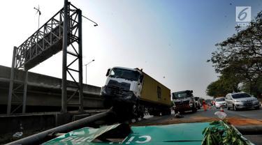 Kendaraan berat kontainer menabrak jalur pembatas pintu masuk tol akses Tanjung Priok di Jalan Raya Cilincing, Jakarta Utara, Sabtu (17/8/2019). Kejadian pada pukul 03.00 dini hari tadi terjadi akibat sopir mengantuk. Tidak ada korban jiwa dalam kejadian ini. (merdeka.com/Arie Basuki)