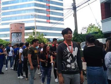 Pegawai kantor berkumpul di luar gedung setelah gempa bumi dahsyat  di Kota Davao, Filipina (29/10/2019). Gempa bumi berkekuatan M 6,8 mengguncang selatan Filipina, Selasa (29/10/2019) pagi waktu setempat. (AP Photo)