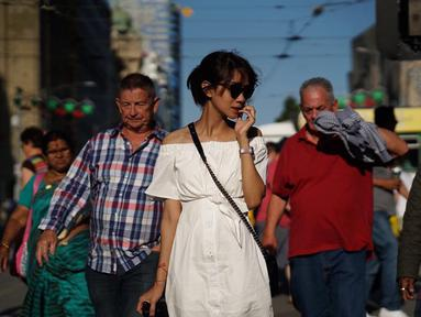 Wanita yang biasa dipanggil Gista ini terlihat cantik saat berjalan di kerumunan orang. Menggunakan pakaian berwarna putih dilengkapi jam tangan dan kacamata hitam, ia tampak sedang memegang kamera di tangan kanannya. (Liputan6.com/IG/@gistaputri)