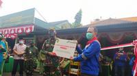 Area Manager PGE Area Karaha Roy Bandoro tengah memberikan simbolis bantuan CSR kepada Danramil Ciawi Kapten Deni Zenal Mutaqin dalam prorgam pemberdayaan ulat maggot dan azola. (Liputan6.com/Jayadi Supriadin)