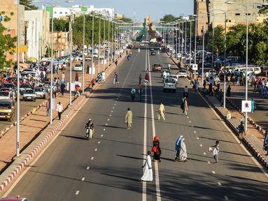 Orang-orang melintasi jalanan di Niamey, Niger (10/7/2019). Niamey adalah ibu kota sekaligus kota terbesar Niger. Penduduknya berjumlah 800,000 jiwa (2000) dengan luas wilayah 670 km².  (AFP Photo/Issouf Sanogo)