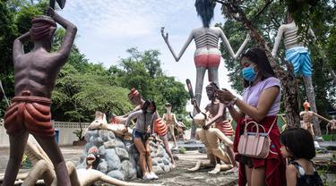 Para pengunjung mengambil foto di depan patung-patung yang menggambarkan nasib orang-orang yang tidak menjunjung tinggi lima ajaran Buddha di sebuah taman yang menggambarkan neraka versi Buddha di kuil Wat Saeng Suk di provinsi pantai Thailand Chonburi (9/7/2020). (AFP/Lillian Suwanrumpha)