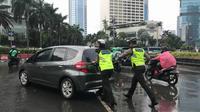 Dua anggota Polisi Lalu Lintas mendorong sebuah mobil Honda Jazz di kawasan Bundaran HI, Jakarta, Selasa (30/1/2018). (Facebook Felicia Siahaan)