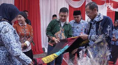 Kepala Departemen Komunikasi Perusahaan Semen Indonesia Sigit Wahono (tengah) bersama Bupati Magetan Suprawoto (kanan) mengamati batik ciprat karya siswa SMA/SMK/MA yang dipamerkan dalam acara #MembangunKemandirian di SMAN 1 Magetan Jawa Timur (2/5/2019). (Liputan6.com/HO/Eko)