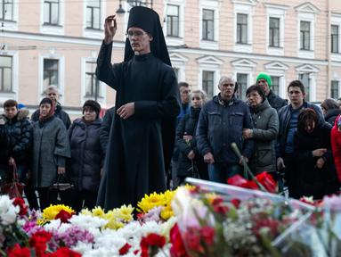 Seorang pendeta memimpin doa saat peringatan simbolik di stasiun kereta bawah tanah Technologicheskiy Institute di St. Petersburg, Rusia, Selasa (4/4). Dikabarkan 10 orang meninggal dalam tragedi tersebut. (AP Photo / Dmitri Lovetsky)