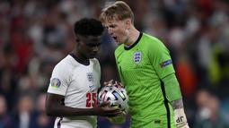 Kiper Inggris Jordan Pickford (kanan) menyemangati rekan setimnya Bukayo Saka saat adu penalti dengan Italia pada pertandingan Euro 2020 di Stadion Wembley, London, Inggris, Minggu (11/7/2021). Italia menang 3-2 lewat adu penalti usai bermain imbang 1-1. (Laurence Griffiths/Pool via AP)