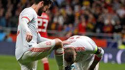 Sergio Ramos mencium sepatu rekan setimnya Isco Alarcon usai mencetak gol kedua saat pertandingan persahabatan melawan Argentina di stadion Wanda Metropolitano di Madrid (27/3). Pada pertandingan itu Spanyol menang 6-1. (AP Photo / Paul White)