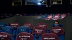 Seorang pria yang memakai masker menunggu di dalam bioskop Cineteca Nacional saat pelonggaran pembatasan di Mexico City, Rabu (12/8/2020). Setelah ditutup hampir lima bulan akibat Corona, bioskop di ibu kota Meksiko dibuka kembali dengan kapasitas 30 persen. (ALFREDO ESTRELLA/AFP)