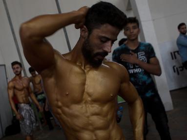Binaragawan Palestina mempersiapkan diri sebelum kompetisi binaraga lokal di Gaza, 26 Oktober 2018. Sementara ribuan warga Palestina melakukan protes di perbatasan dengan Israel, ratusan lainnya memadati gedung olahraga untuk kompetisi. (AP/Khalil Hamra)