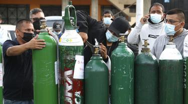 Para pria menyesuaikan tangki oksigen kosong saat antre menunggu toko isi ulang di Callao, Peru, Senin (25/1/2021). Di tengah pandemi COVID-19, beberapa orang mengatakan mereka telah antre sehari sebelumnya untuk menjadi yang pertama saat toko buka. (AP Photo/Martin Mejia)