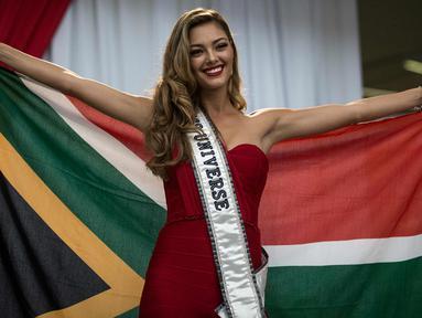 Miss Universe 2017 Demi-Leigh Nel-Peters berpose dengan bendera Afrika Selatan saat tiba di Bandara Internasional OR Tambo di Johannesburg (24/1). Untuk pertama kalinya setelah dinobatkan Demi Leigh baru pulang ke Afrika Selatan. (AFP Photo/Gulshan Khan)