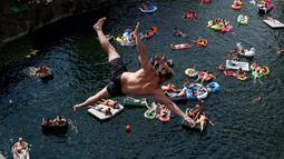 Penonton menyaksikan peserta terjun ke dalam air selama kompetisi melompat dari tebing di dekat desa Hrimezdice, Republik Ceko, 3 Agustus 2018. Kegiatan ini menjadi sebuah olahraga yang ditandai dengan keberanian, sensasi dan resiko. (AP/Petr David Josek)