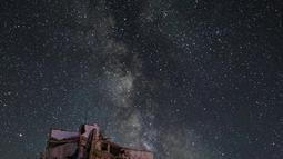Galaksi Bima Sakti menghiasi langit malam saat seorang pria berjalan melewati gedung-gedung yang hancur akibat pengeboman di Kota Ariha, Provinsi Idlib, Suriah, Sabtu (27/6/2020). (Omar HAJ KADOUR/AFP)